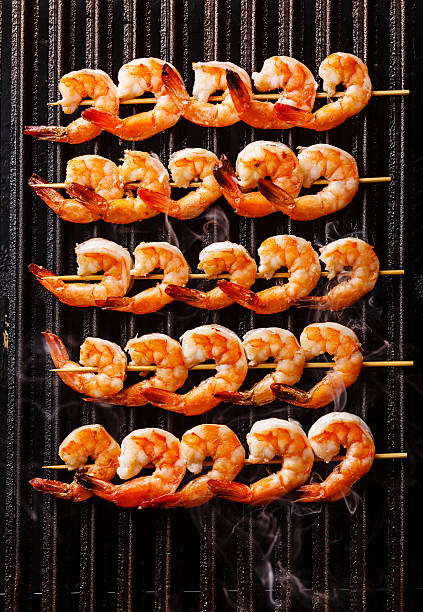 grilled fried prawns on skewers on grill - gegrillte garnelen stock-fotos und bilder