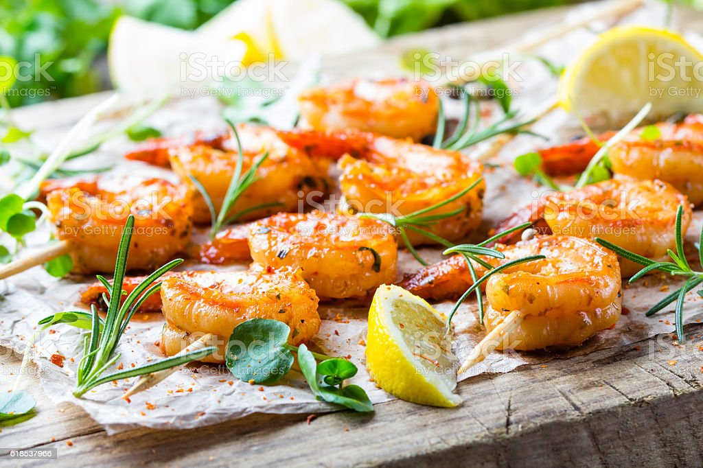 Grilled fried Shrimps Prawns on wooden skewers with spices stock photo
