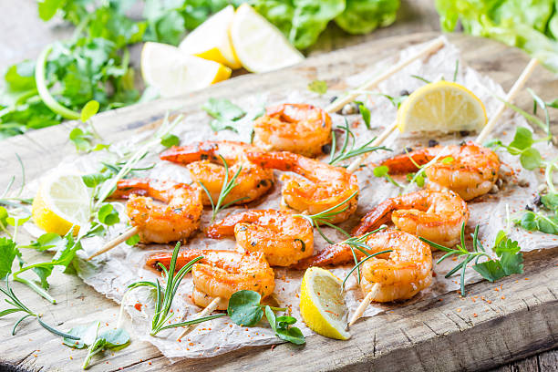grilled fried shrimps prawns on wooden skewers with spices - gegrillte garnelen stock-fotos und bilder