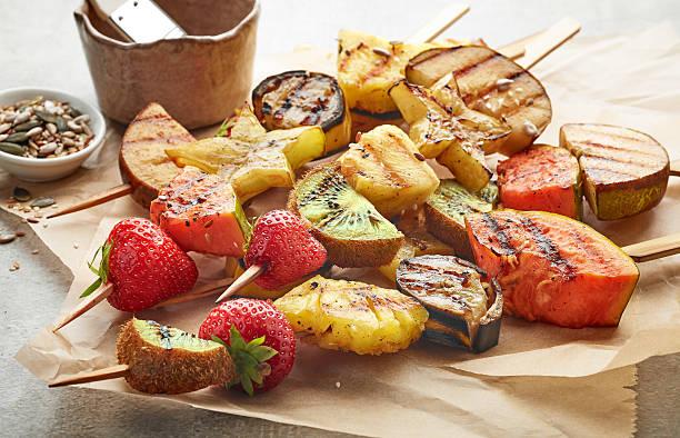 grilled fruit pieces on wooden skewers - gebackene banane stock-fotos und bilder