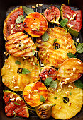Grilled fruits; pineapples, peaches, figs, pears and watermelon with pine nuts, fresh herbs and honey on the grill plate, top view. Gourmet, healthy fruit dessert