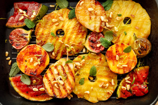 gegrillte früchte; ananas, pfirsiche, feigen, birnen und wassermelone mit pinienkernen, frischen kräutern und honig auf der grillplatte, ansicht von oben. - melonenbirne stock-fotos und bilder