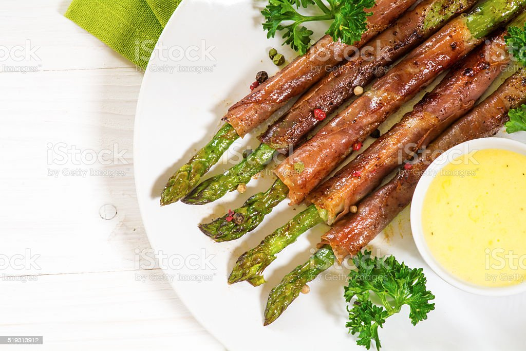 grilled green asparagus wrapped in bacon,white wood stock photo