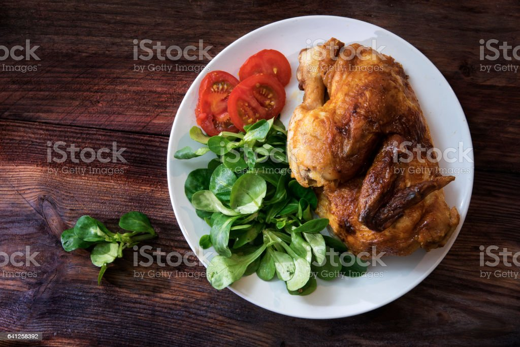 grilled half chicken, tomatoes and corn salad, dark rustic wood stock photo