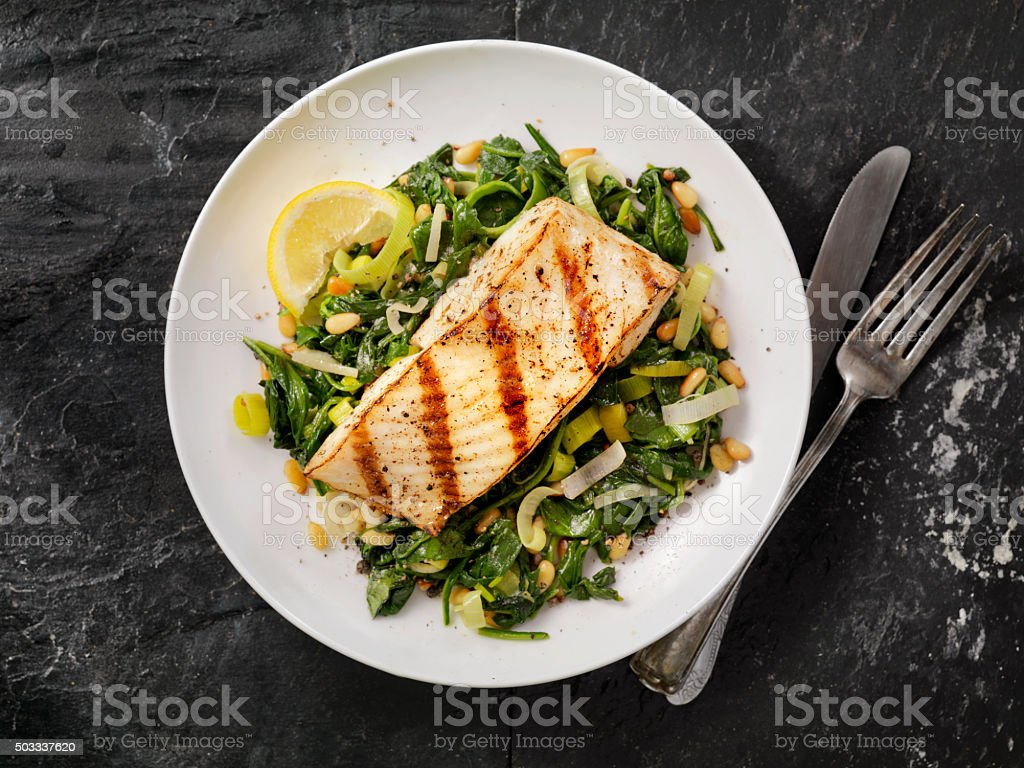 Grilled Halibut with Spinach, leeks and Pine Nuts royalty-free stock photo