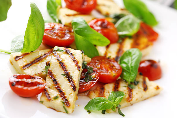 Grilled halloumi cheese with roasted tomatoes and basil stock photo