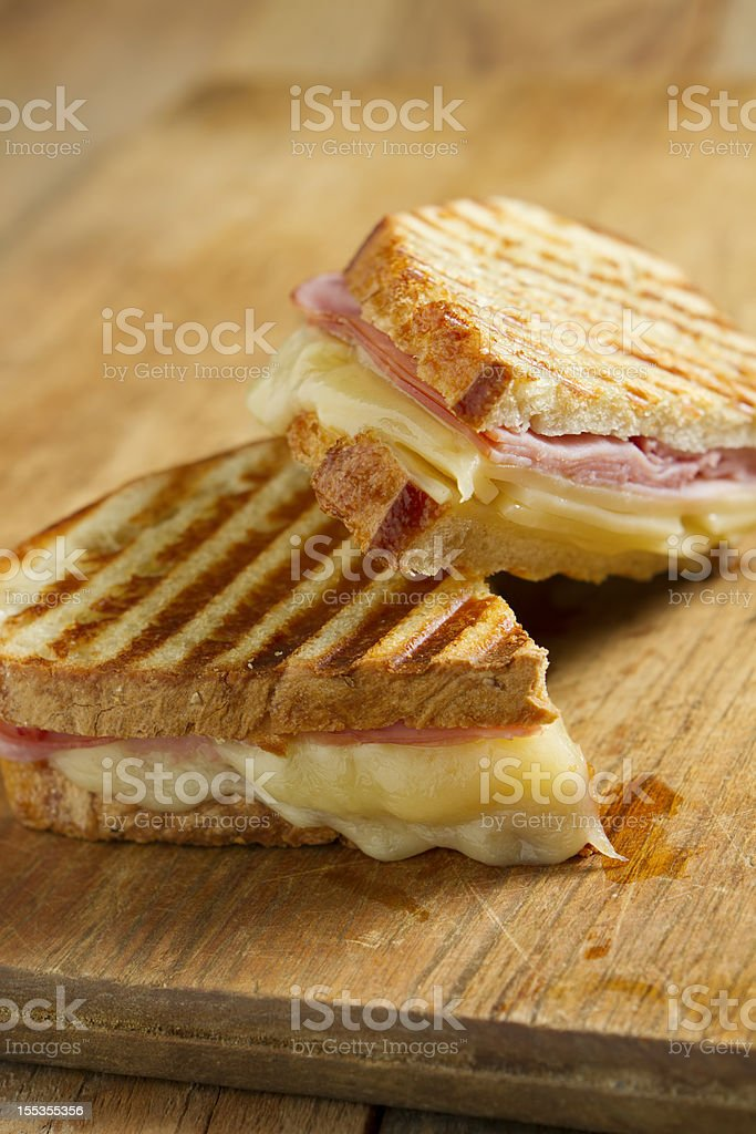 Grilled ham and cheese panini sandwich on wood table stock photo