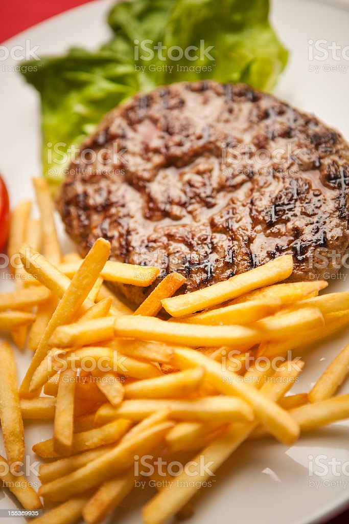 Grilled hamburger with fries, tomato and salad royalty-free stock photo