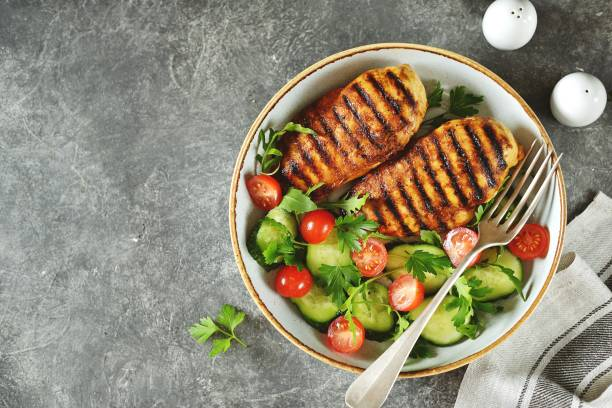 Grilled healthy chicken breast with a salad of cherry tomatoes, cucumbers, arugula and parsley. Top view. stock photo
