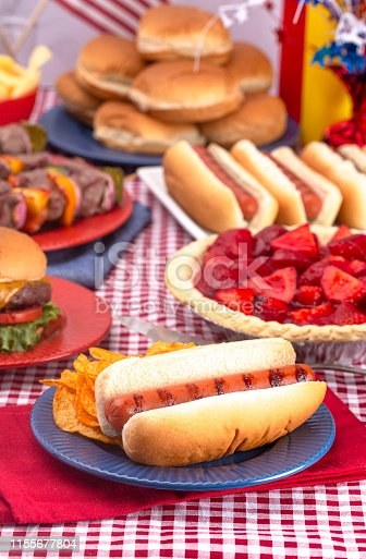 534317162 istock photo Grilled Hot Dog on a Table Set for an American BBQ with Red White and Blue 1155677804