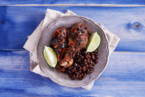 grilled jamaican jerk chicken with black beans shot top down grilled jamaican jerk chicken with black beans shot top down on wooden table painted blue overhead projector stock pictures, royalty-free photos & images