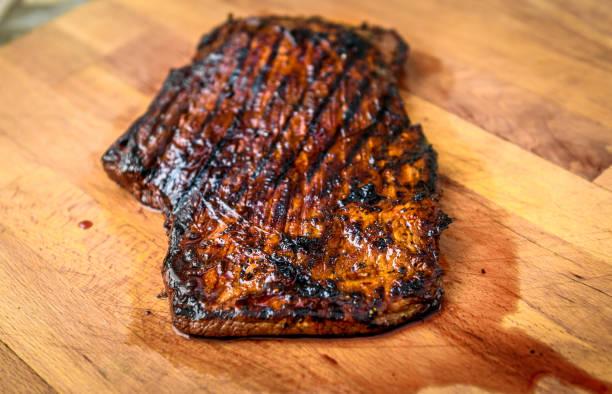 gegrilltes saftig mariniertes rinderflankiersteak auf holzbrett. - flank steak marinaden stock-fotos und bilder