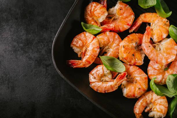 grillade jätteräkor på pan på mörka bord - räka fisk och skaldjur bildbanksfoton och bilder