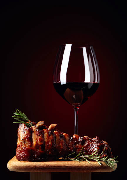 Grilled lamb ribs with rosemary and red wine on a wooden board. stock photo