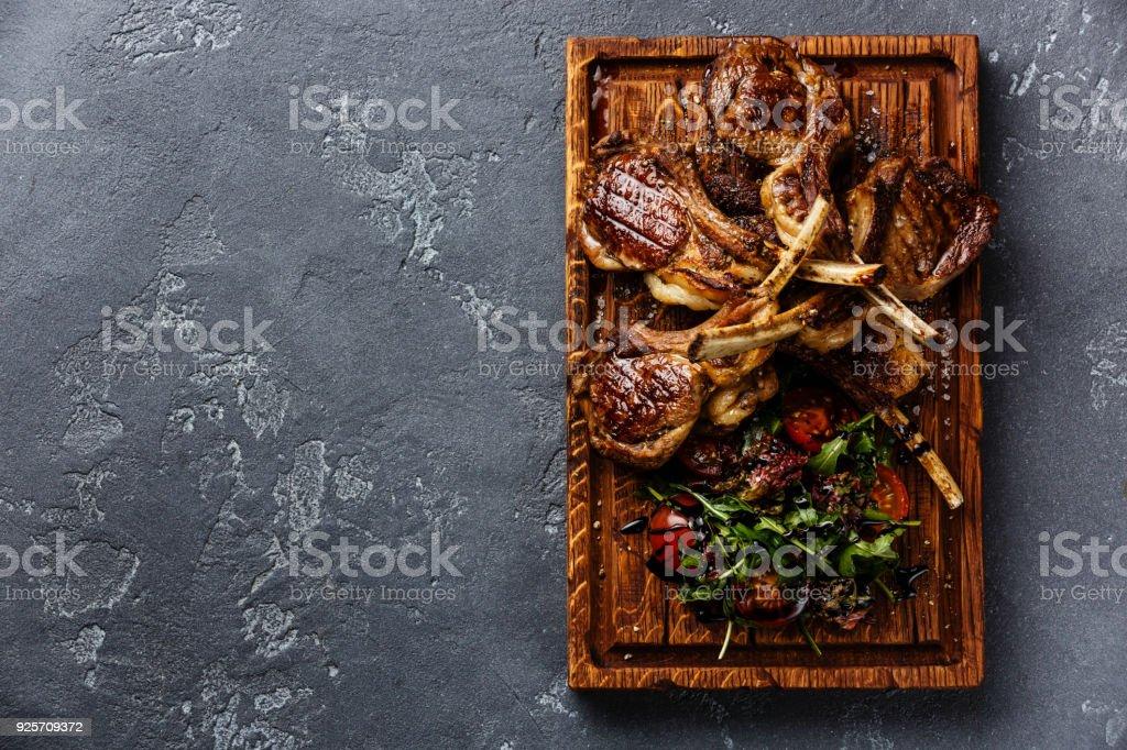 Grilled lamb ribs with tomatoes and arugula salad stock photo