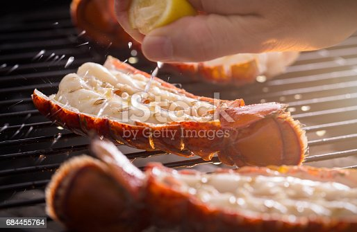 Fresh cold water lobster tails being cooked on a outdoor grill with fresh lemon juice being squeezed on the tails.