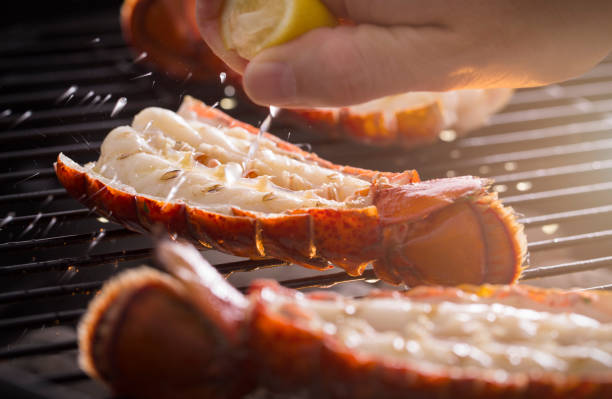 grilled lobster tail on the grill with lemon - tail stock photos and pictures