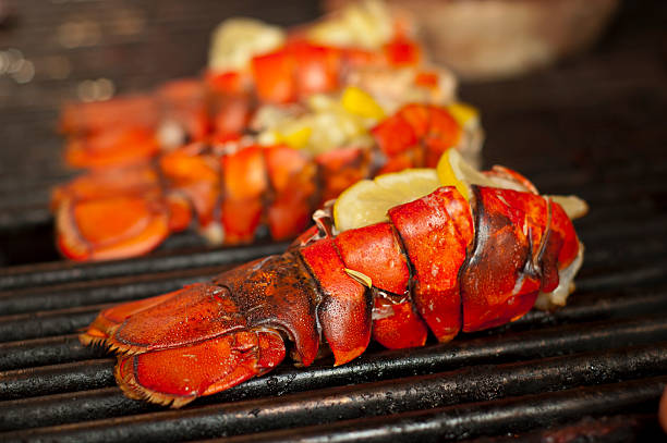 Grilled lobsters with lemons on a grill stock photo
