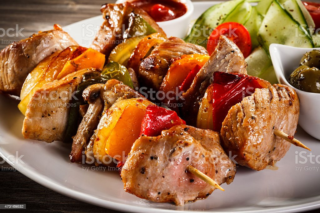 Grilled meat and vegetable kebab served with vegetable salad stock photo