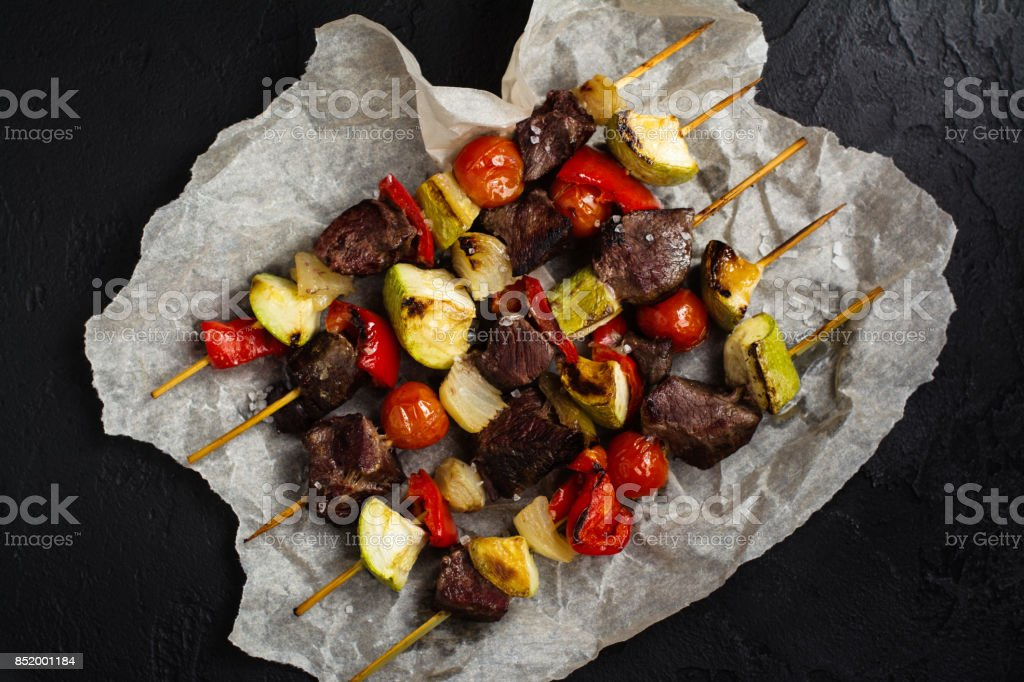 Grilled meat and vegetables cabobs over black stone table stock photo