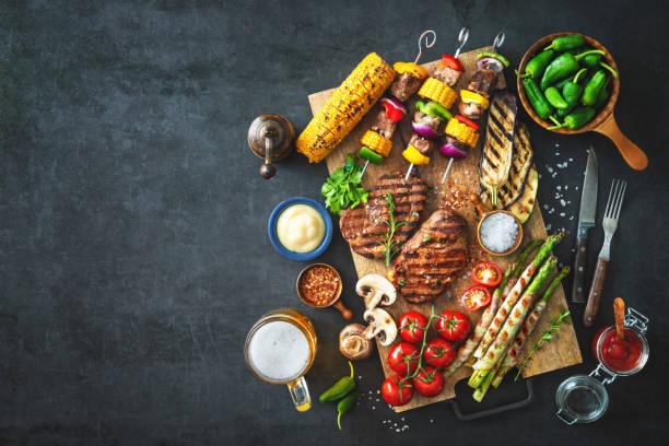 Carnes a la brasa y verduras en placa de piedra rústica - foto de stock
