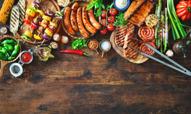 Grilled meat and vegetables on rustic wooden table stock photo
