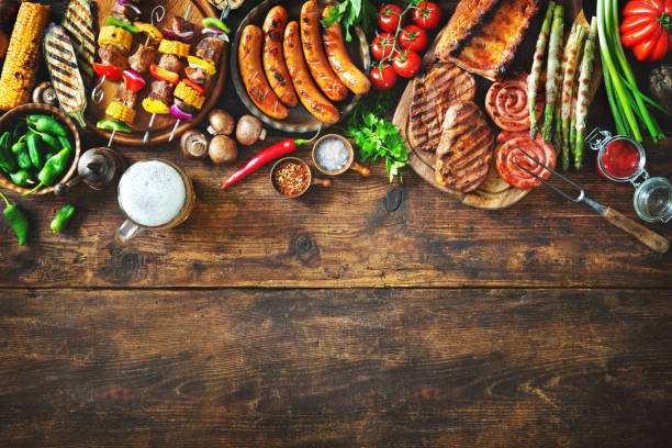grilled meat and vegetables on rustic wooden table - barbecue grill stock photos and pictures