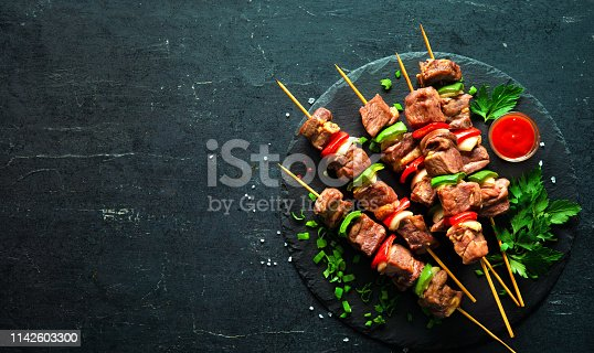 655794674 istock photo Grilled meat and vegetables on skewers 1142603300