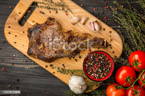 916096852 istock photo Grilled meat barbecue steak with spices, herbs, garlic and tomato. Top View 1202820969