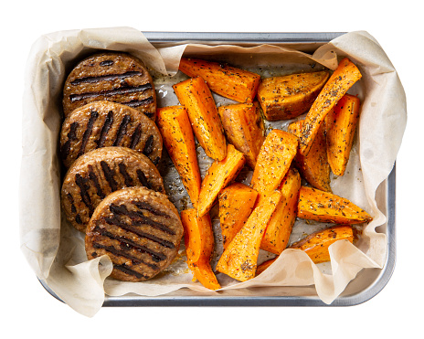 Grilled meat free plant based cutlets with sweet potato wedges in metal baking dish isolated on white. Healthy vegan or vegetarian food concept. Top view.