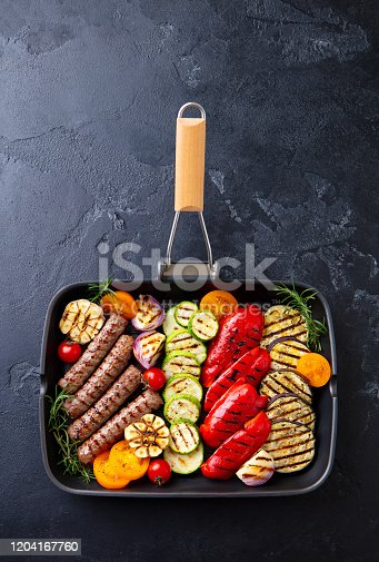 655793486 istock photo Grilled meat kebab and vegetables in grill pan. Black stone background. Top view. 1204167760