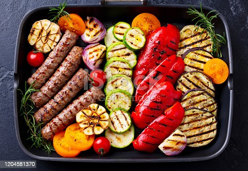655793486 istock photo Grilled meat kebab and vegetables in grill pan. Black stone background. Top view. 1204581370