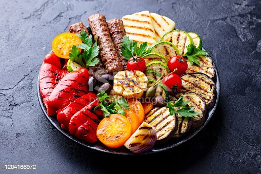655793486 istock photo Grilled meat kebabs and vegetables on a plate. Black stone background. Close up. 1204166972