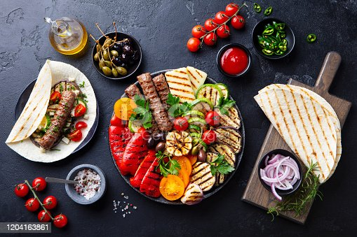 655793486 istock photo Grilled meat kebabs, vegetables on a black plate with tortillas, flat bread. Slate stone background. Top view. 1204163861