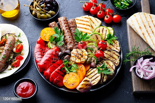 655793486 istock photo Grilled meat kebabs, vegetables on a black plate with tortillas, flat bread. Slate stone background. 1204165345