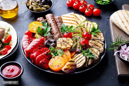655793486 istock photo Grilled meat kebabs, vegetables on a black plate with tortillas, flat bread. Slate stone background. Close up. 1204581421