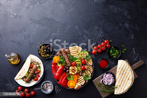 655793486 istock photo Grilled meat kebabs, vegetables on a black plate with tortillas, flat bread. Slate background. Copy space. Top view. 1254946790