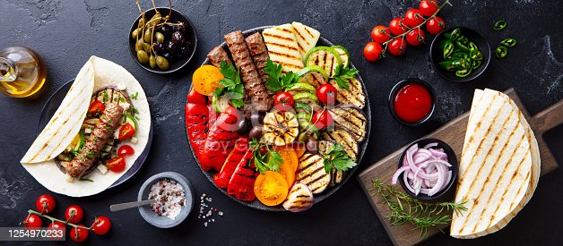 655793486 istock photo Grilled meat kebabs, vegetables on a black plate with tortillas, flat bread. Slate background. Top view. 1254970233