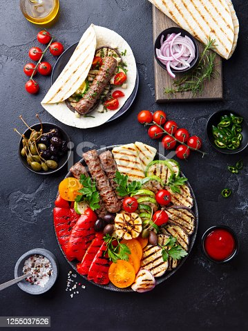 655793486 istock photo Grilled meat kebabs, vegetables on a black plate with tortillas, flat bread. Slate background. Top view. 1255037526