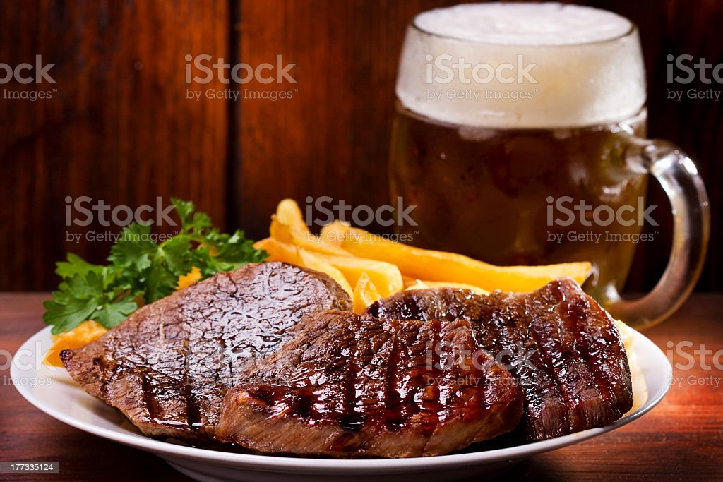 Grilled meat plated with vegetables and cold beer stock photo