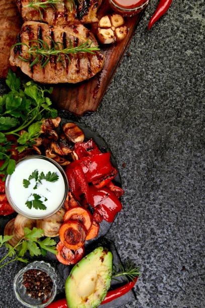 Gegrilltes Fleisch. Steak Schweinegrill auf Holz-Schneidebrett mit einer Vielzahl von gegrilltem Gemüse auf schwarzem Hintergrund Top-Ansicht. Flach liegen. Kopieren Sie den Speicherplatz. – Foto