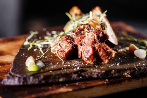 gegrilltes fleisch mit gemüse, gewürze auf einer steinplatte und holz hintergrund. selektiven fokus - grillstein stock-fotos und bilder