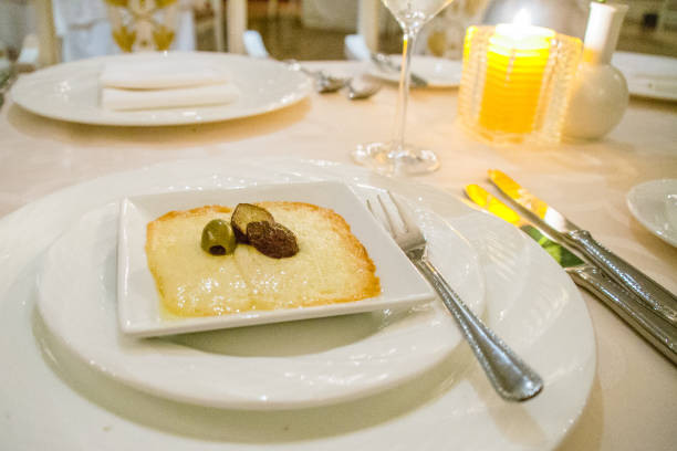 grilled melted gruyere cheese appetiser topped with black and greeen olives on a square plate - appetiser stock photos and pictures
