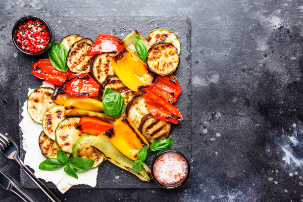 grilled multicolored vegetables, aubergines, zucchini, pepper with green basil on serving stone board - prażony zdjęcia i obrazy z banku zdjęć