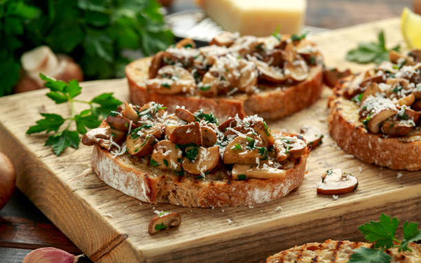 Grilled mushroom toast with parsley, lemon and parmesan cheese on wooden board. healthy vegan food stock photo