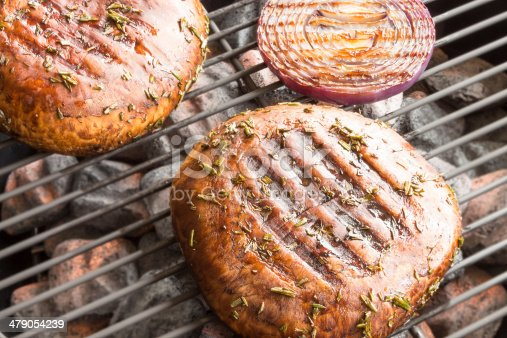 Two portobello mushrooms marinated and grilling with purple onion