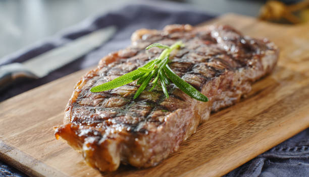 grilled new york strip steak resting on wooden cutting board stock photo