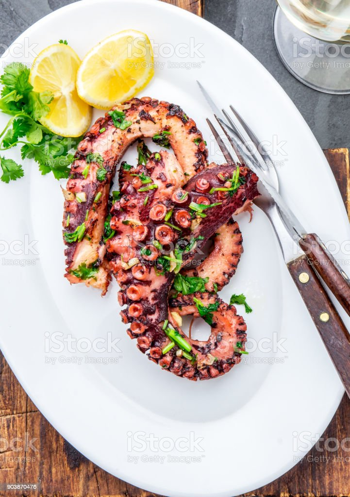Grilled octopus on white plate serverd with white wine , top view. Seafood stock photo