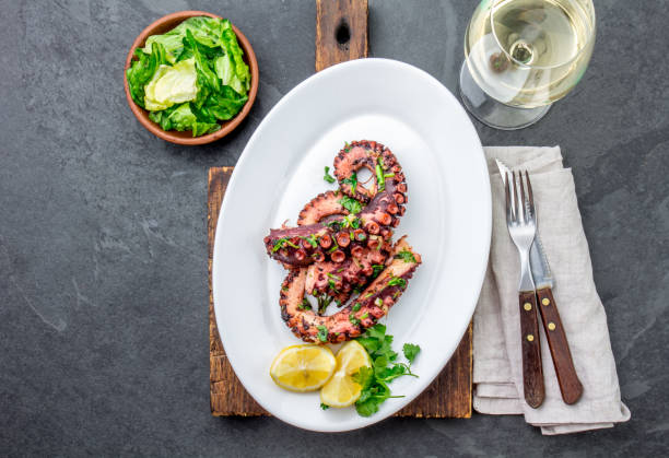 grilled octopus on white plate serverd with white wine , top view. seafood - octopus stock pictures, royalty-free photos & images