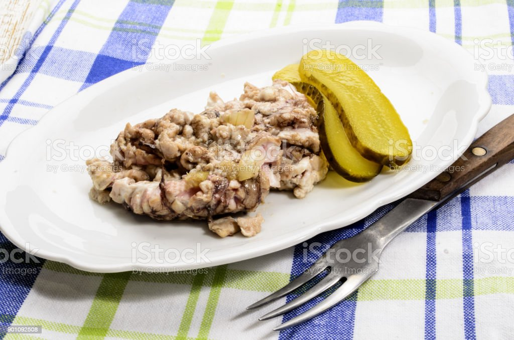 grilled pig brain with onions and gherkin served on a plate stock photo